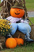 Pumpkin scarecrow wearing hat, shirt and trousers sitting on hay bale
