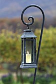 Lit candle in lantern hanging from iron rod with spiral ens