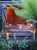 Illuminated wooden shed with sofa, two lanterns and tree fern in garden