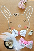 Hand-drawn rabbit decorated with fabric bow, quails' eggs & feathers