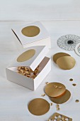 Hand-crafted cardboard boxes for storing punched gold confetti