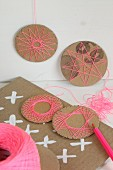 Selbstgemachte Dekoration aus Pappkreisen mit Fadenmustern
