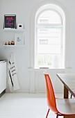 Blick auf Rundbogenfenster in hell gestalteter Küche einer Altbauwohnung