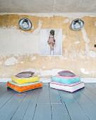 Bunt gestapelte Bodenkissen vor patinierter Wand mit Retrowandleuchten und Bild