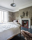 Sleigh bed in country-house bedroom with vintage patinated walls