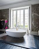 Oval, free-standing designer bathtub on stone tiles in front of bedroom window
