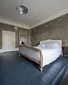 Sleigh bed on slate grey wooden floor in bedroom with patinated walls