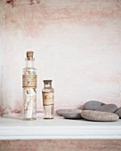 Two corked glass bottles with vintage labels and flat pebbles in front of patinated wall