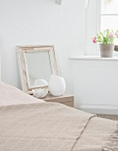 Mirror with vintage wooden frame and ornaments on bedside table, woollen blanket on bed and potted plant on windowsill