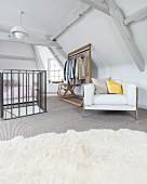 Schlafbereich in ausgebautem Dachraum mit Retro Designersessel und Kleiderständer