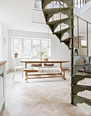 Vintage spiral staircase in front of dining table, bench and chairs