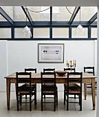 Rustikaler Esstisch und Stühle aus Holz im Anbau mit Glasdach