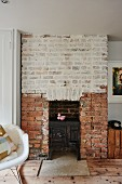 Cast iron stove in old brick fireplace with whitewashed upper section in living room