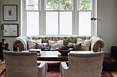 Traditional couch set with ecru upholstery and retro chrome standard lamp in front of window