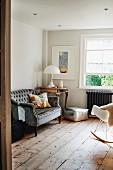Antikes Sofa neben Vintage Tisch mit Klassiker Tischleuchte in rustikalem Wohnzimmer mit Holzdielenboden