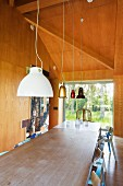 Two dining table pushed together below various pendant lamps in wood-panelled dining room