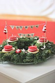 Advent wreath decorated with Father Christmas figurines and lettering on bunting with festive greeting in German