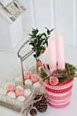 Weihnachtliches Kerzengesteck in Glas verziert mit rot-weissen Bändern