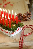 Christmas arrangement of red candles and baubles