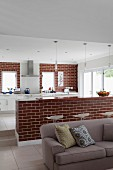 Sofa in open-plan living area in front of brick counter and kitchen counter against brick wall in background