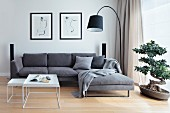 Nest of white coffee tables in front of grey sofa combination, black arc lamp and bonsai tree