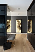 Hallway lined with black, glossy fitted cupboards leading to large portrait on dark wall