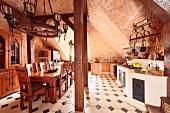 Gewölbe in rustikaler Küche mit Essplatz aus Massivholz, Fliesenboden mit dunklen Einlegern, im Mittelalter-Stil