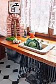 Rustikales Spülbecken aus Stein in Holzplatte vor Fenster eingebaut