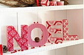 Christmas arrangement of cardboard letters covered in fabric scraps