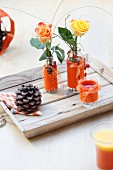 Roses in glass vases decorated with orange felt covers