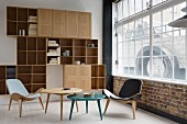 Classic easy chairs with covers in different colours and side tables in front of shelving unit with open compartments and cabinet doors in corner of loft apartment