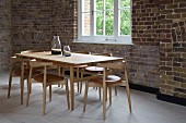 Dining area with classic chairs around wooden table in loft interior with rustic brick wall