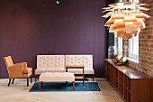 Armchair with beige upholstery, pale sofa and ottoman against purple wall; PH Artichoke Pendant lamp in foreground