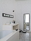 Fitted bathtub, masonry washstand and full-length mirror against whitewashed brick walls