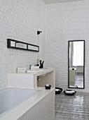 Eingebaute Badewanne und gemauerter Waschtisch vor geweisselter Ziegelwand, im Hintergrund Wandspiegel