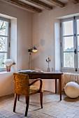 Upholstered armchair at antique desk in corner