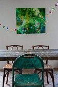 Vintage metal chair and Thonet chairs at wooden dining table in front of bunting and artwork on wall