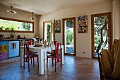 Eclectic kitchen with dining area and windows leading to terrace