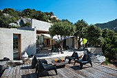 Modern plastic chairs on terrace of Mediterranean bungalow surrounded by olive trees