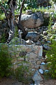 Outdoor shower on wall at foot of boulder-covered slope