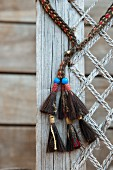 Ethnic tassels and weathered net attached to board