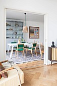 View of retro chairs with green upholstery and white table in dining room seen from living room through open sliding door