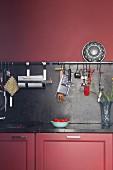 Altrosa Küchenzeile mit Arbeitsplatte und Spritzschutz aus dunklem Stein