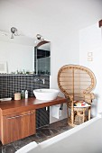 Rattan peacock armchair next to modern wooden washstand with base cabinet and countertop basin