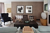 Lounge area with seating around large, low wooden coffee table and black wing-back chair in to one side