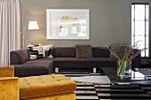 Yellow chaise longue and dark corner sofa around coffee table