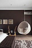 White, wicker, hanging chair in bedroom with wall painted dark brown