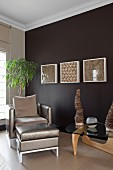 Armchair and footstool with silver, shiny upholstery and classic coffee table in front of white-framed glass cases on wall painted dark brown