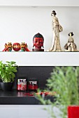 Oriental ceramic figurines and head of Buddha on white shelf
