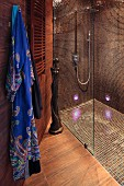Shower areas with glass partition, brown mosaic tiles on walls and floor and dressing gown hanging to one side in designer bathroom